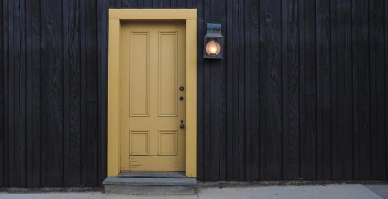 Gele deur zwarte gevel